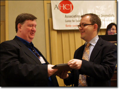 Mike Berens (left) accepts his Award for Excellence in Health Care Journalism from AHCJ Board President Charles Ornstein.